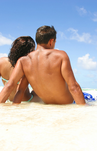 Couple-sitting-on-the-beach-after-achieving-debt-relief