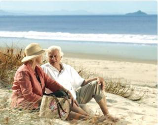 Retirement-couple-sitting-on-beach-debt-free